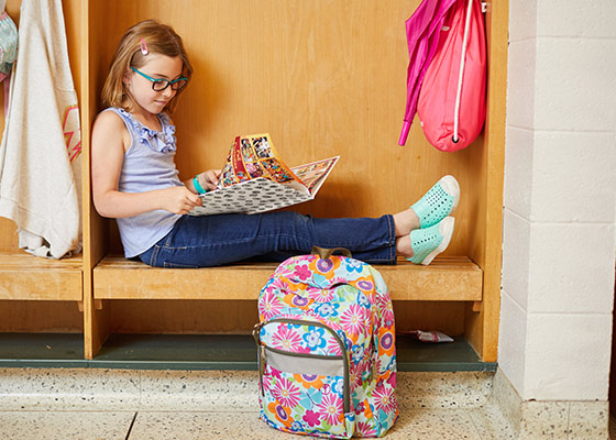 elementary school girl sitting in locker reading a yearbook, reading a yearbook at school