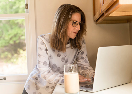 Woman standing at counter looking at laptop with glass of milk