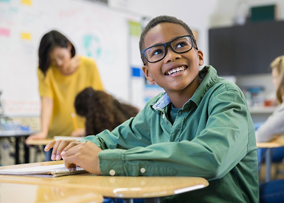 young boy with olive green shirt and glasses looking up at a teacher with a smile