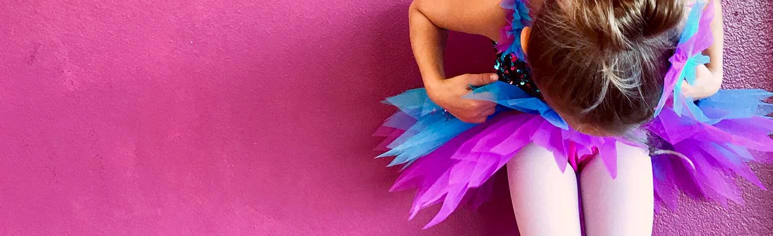 young girl in purple and blue tutu dance costume looking down at her toes on pink wall